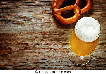 beer and pretzel on a dark wood background. tinting....