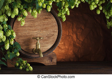 Beer barrel with fresh hops on wooden table still-life
