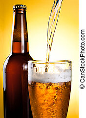 Beer Being Poured in Glass and Bottle on yellow background