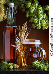 Beer bottle and glass with fresh green hop and wheat on rustic wooden table still life