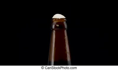 beer bottle on black background closeup. beer foams in a...