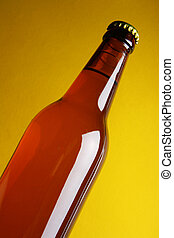 Beer bottle over yellow