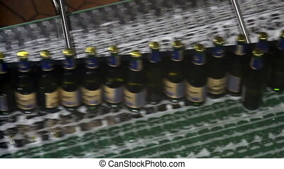 Beer bottles on conveyor of bottling machine