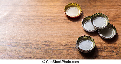 Beer caps on wooden background, copy space