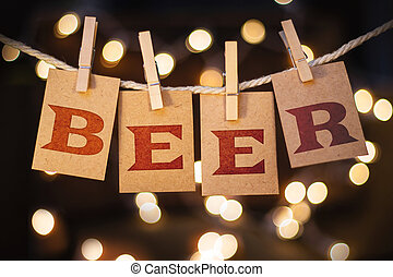 The word BEER printed on clothespin clipped cards in front of defocused glowing lights.
