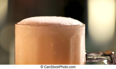 Beer foam and bubbles. Foam bubbles in rotating glass of...