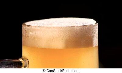 Beer foam scraper using. Close up macro excess beer foam...