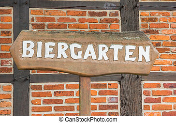 Beer garden sign in front of a half-timbered wall