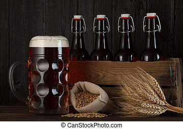 Beer glass on table with crate full of bottles
