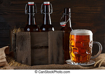 Beer glass with beer bottles in wooden crate on burlap cloth