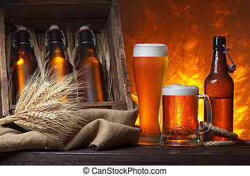 Beer glasses with wooden crate full of beer bottles and wheat ears on table