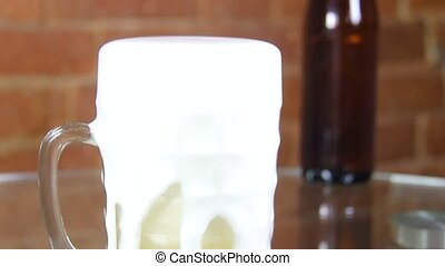 Beer in a large glass mug with high foam very close up against a brick wall. Foam rises and spills out of a glass. High quality FullHD footage