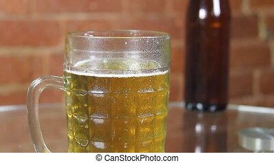 Beer in a large glass mug with high foam very close up against a brick wall. High quality FullHD footage