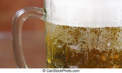 Beer in a large glass mug with high foam very close up. High quality FullHD footage