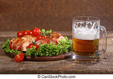 Beer in a transparent mug and chicken beaters in bacon submitted with greens, bread and tomatoes on a wooden table