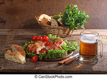 Beer in a transparent mug and chicken beaters in bacon submitted with greens, bread and tomatoes