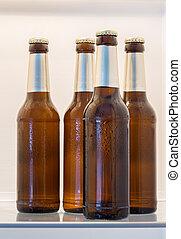 Beer in bottles in open fridge concept