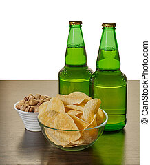 beer in bottles with chips and pistachios