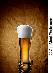 Beer in glass on brown background