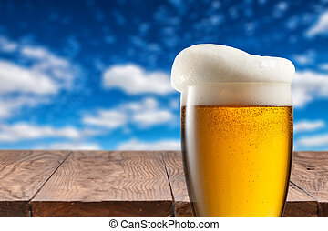 Beer in glass on wooden table against blue sky