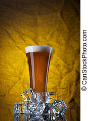 Beer in glass with ice cubes on yellow background