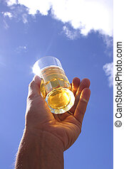 Beer in Hand - Hand with beer glass and blue sky