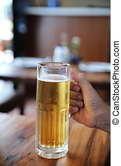 beer in tall glass on wood background with man hand