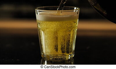 Beer is poured into a glass - Beer is poured from the top...