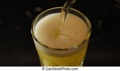Beer is poured into a glass - Beer pouring out of a can into...