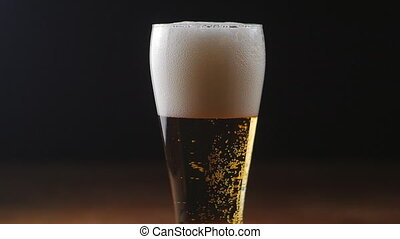 Beer is pouring into glass on black background.