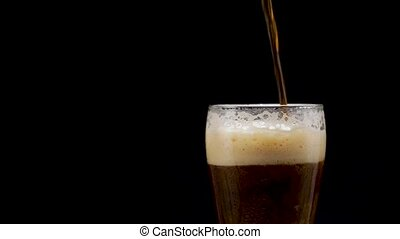 Beer is pouring into glass on black background. dark beer