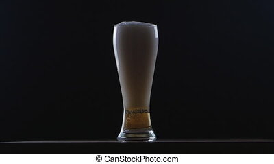 Beer is pouring into glass on black background. Slow motion
