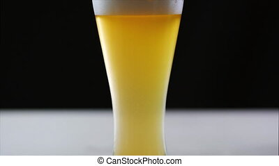Beer is pouring into glass on black background. Slow motion...