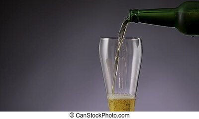 Beer is pouring into glass on gray background.