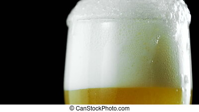 Beer poured in glass against black background 4k - Close-up ...