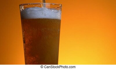 Beer poured in glass on background.