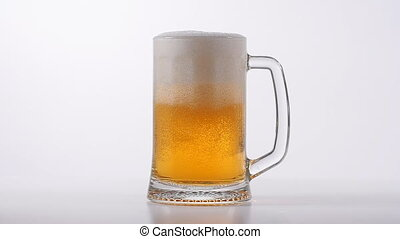 Beer poured into glass on white background in slow motion