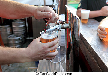 Pouring beer to plastic glass from beer tap