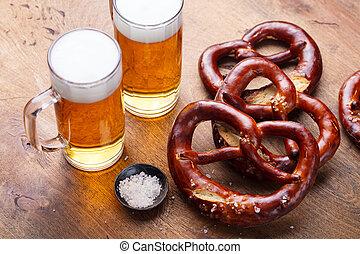 Beer, salted pretzels, potato chips on wooden background.