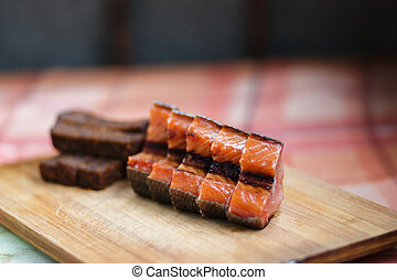 Beer snack. Fried black bread and red smoked fish. Black bread and smoked fish cut into pieces, lie on a wooden Board.