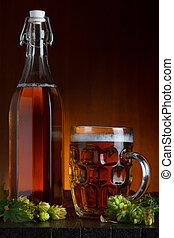 Beer still-life with fresh green hop on rustic wooden table