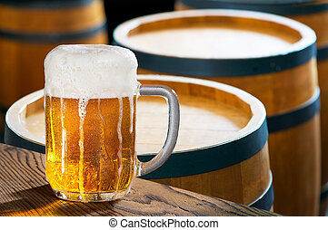 beer - glass of beer with old wooden barrels