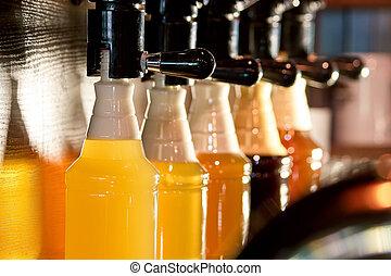 Beer taps beer pouring in bottles.