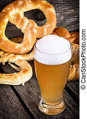 beer with pretzels on wooden table
