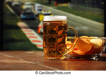 Beer with snack on a table against formula one race background. Sport and entertainment concept