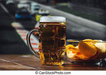 Beer with snack on a wooden table against formula one race background. Sport and entertainment concept