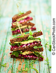 sandwich with beet, cheese, avocado and arugula