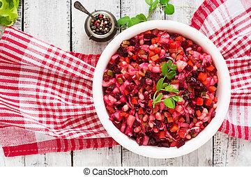 Beet salad Vinaigrette in a white bowl. Top view