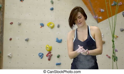 Before climbing wall woman treats hands with magnesia.