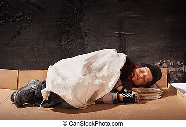 Beggar boy sleeping on cardboard sheet in the dark - with...